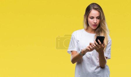 Photo pour Belle jeune femme blonde à l'aide de smartphone sur fond isolé peur en état de choc avec un visage de surprise, peur et excité par l'expression de la peur - image libre de droit