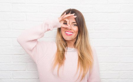 Young adult woman over white brick wall wearing winter outfit at home doing ok gesture with hand smiling, eye looking through fingers with happy face.