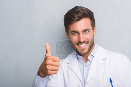 Photo for Handsome young professional man over grey grunge wall wearing white coat doing happy thumbs up gesture with hand. Approving expression looking at the camera with showing success. - Royalty Free Image