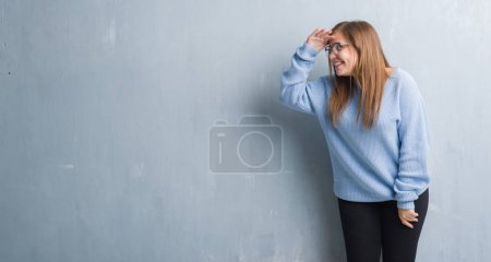 Photo for Young adult woman over grey grunge wall wearing glasses very happy and smiling looking far away with hand over head. Searching concept. - Royalty Free Image