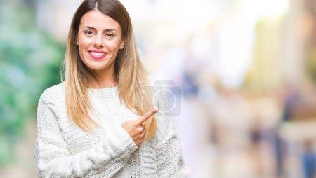 Photo pour Chandail blanc occasionnels de belle jeune femme sur fond isolé joyeux avec un sourire de face montrant avec la main et des doigts jusqu'à la côte avec une expression heureuse et naturelle sur le visage en regardant la caméra - image libre de droit