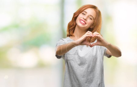Young beautiful woman over isolated background smiling in love showing heart symbol and shape with hands. Romantic concept.