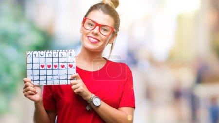 Photo pour Belle jeune femme tenant calendrier menstruation sur fond isolé avec un visage heureux, debout et souriant avec un sourire confiant, montrant les dents - image libre de droit