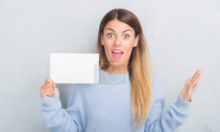 Photo for Young adult woman over grey grunge wall holding blank card very happy and excited, winner expression celebrating victory screaming with big smile and raised hands - Royalty Free Image