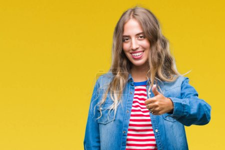 Photo for Beautiful young blonde woman over isolated background doing happy thumbs up gesture with hand. Approving expression looking at the camera with showing success. - Royalty Free Image