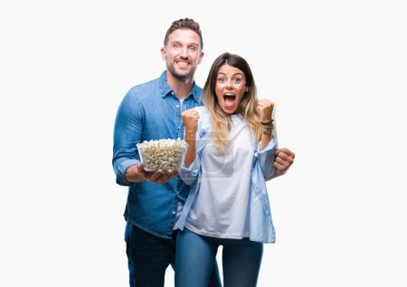 Young couple in love eating popcorn over isolated background screaming proud and celebrating victory and success very excited, cheering emotion