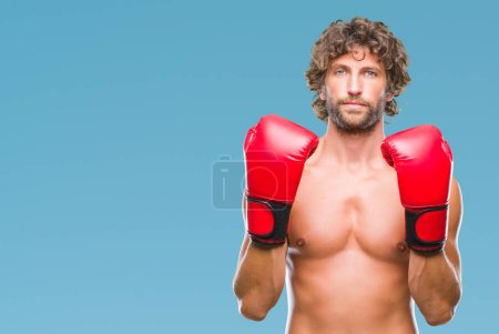 Handsome hispanic boxer man wearing boxing gloves over isolated background with serious expression on face. Simple and natural looking at the camera.
