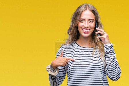 Beautiful young blonde woman talking on smarpthone over isolated background with surprise face pointing finger to himself