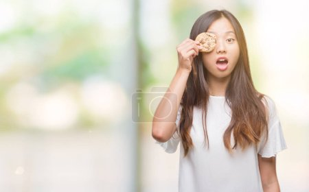 Young asian woman eating chocolate chip cookie ove...