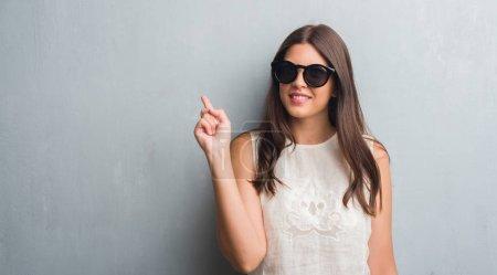 Photo pour Jeune femme brune au fil gris grunge mur portant lunettes de soleil mode surpris avec une idée ou un doigt pointé avec visage heureux, numéro un de la question - image libre de droit