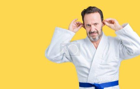 schöner älterer Mann mittleren Alters in Kimono-Uniform über isoliertem Hintergrund, lächelnd, die Ohren mit den Fingern zuziehend, lustige Geste. Vorsprechen-Problem