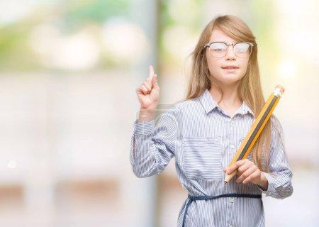 Photo pour Jeune enfant blonde tenant gros crayon surpris avec un doigt pointé, idée ou question, avec le visage heureux, numéro un - image libre de droit