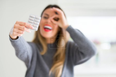 Young beautiful woman holding pharmaceutical pills at home with happy face smiling doing ok sign with hand on eye looking through fingers