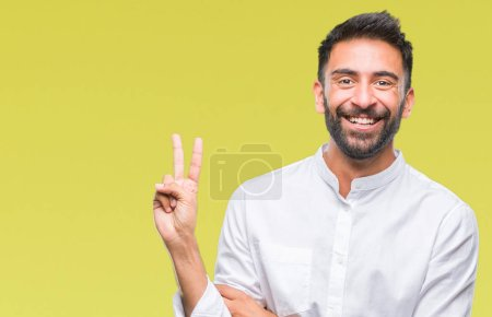 Adult hispanic man over isolated background smiling with happy face winking at the camera doing victory sign. Number two.