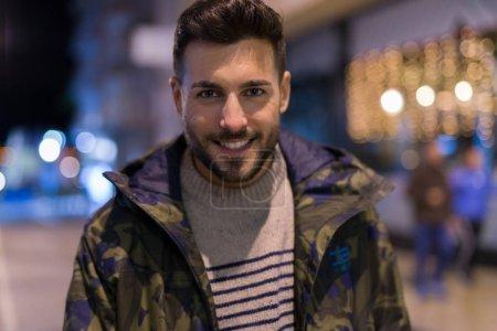 Photo pour Jeune homme beau posant et souriant. Street style la nuit - image libre de droit