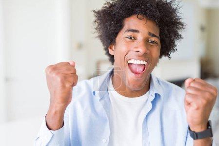 Photo pour L'homme afro-américain chez lui excité par le succès avec les armes levées célébrant la victoire en souriant. Concept gagnant . - image libre de droit