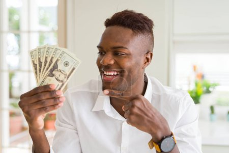 Photo for African american man holding twenty dollars bank notes very happy pointing with hand and finger - Royalty Free Image