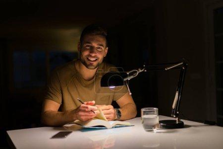 Młody przystojny mężczyzna, nauki w domu z książką w nocy. SM