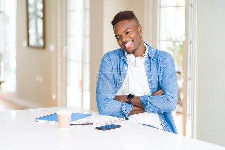 Photo pour Étudiant afro-américain étudiant utilisant des cahiers et portant un casque heureux visage souriant avec les bras croisés en regardant la caméra. Personne positive . - image libre de droit