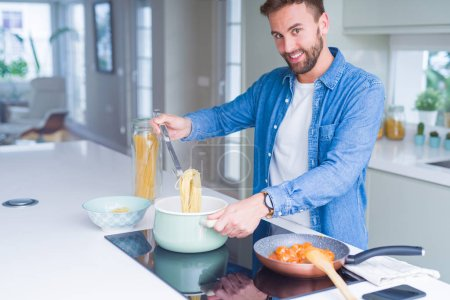 Handsome man cooking pasta at home