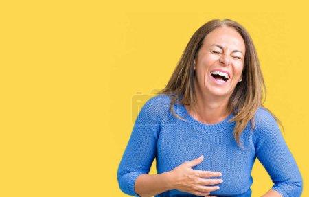 Photo pour Moyen-âge belle femme portant un pull d'hiver sur fond isolé Sourire et rire fort à haute voix parce que drôle blague folle. Bonne expression . - image libre de droit