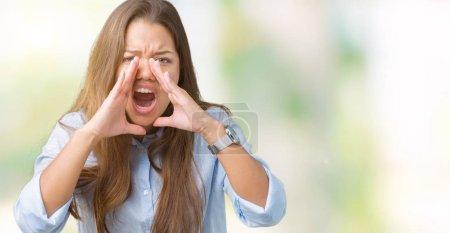 Photo pour Jeune belle femme d'affaires brune sur fond isolé criant à haute voix avec les mains sur la bouche - image libre de droit