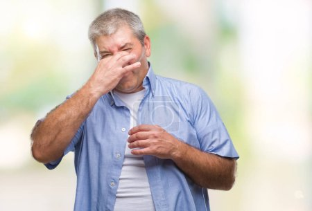 Photo for Handsome senior man over isolated background smelling something stinky and disgusting, intolerable smell, holding breath with fingers on nose. Bad smells concept. - Royalty Free Image