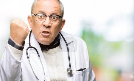 Photo for Handsome senior doctor man wearing medical coat angry and mad raising fist frustrated and furious while shouting with anger. Rage and aggressive concept. - Royalty Free Image