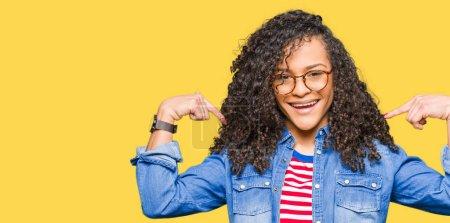 Photo pour Jeune belle femme aux cheveux bouclés portant des lunettes regardant confiant avec le sourire sur le visage, se pointant avec les doigts fiers et heureux . - image libre de droit