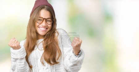 Photo for Young beautiful brunette hipster woman wearing glasses and winter hat over isolated background celebrating surprised and amazed for success with arms raised and open eyes. Winner concept. - Royalty Free Image