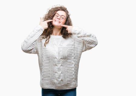 Photo pour Belle brune cheveux bouclés jeune fille porter Pull hiver sur fond isolé souriant montrant confiants et en pointant avec la bouche et des dents de doigts. Concept santé. - image libre de droit