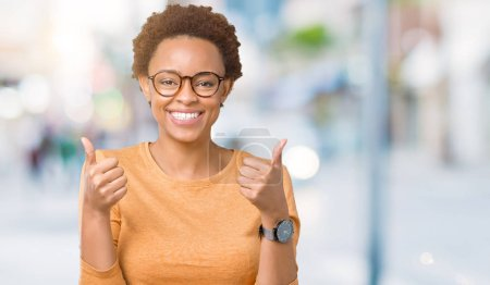 Photo for Young beautiful african american woman wearing glasses over isolated background success sign doing positive gesture with hand, thumbs up smiling and happy. Looking at the camera with cheerful expression, winner gesture. - Royalty Free Image