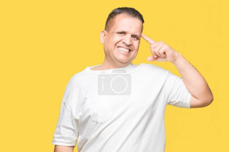 Photo for Middle age arab man wearig white t-shirt over isolated background Smiling pointing to head with one finger, great idea or thought, good memory - Royalty Free Image