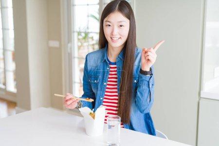 Photo pour Belle femme asiatique mangeant le riz asiatique dans la boîte de livraison très heureux pointant avec la main et le doigt sur le côté - image libre de droit