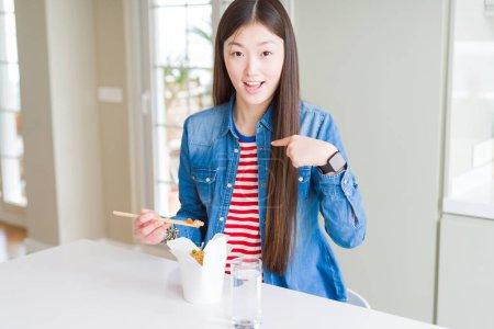 Photo pour Belle femme asiatique mangeant le riz asiatique dans la boîte de livraison avec le visage de surprise pointant le doigt à lui-même - image libre de droit