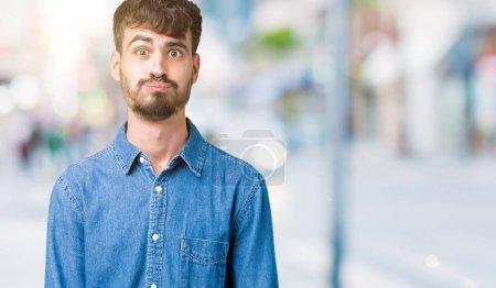 Photo pour Jeune homme beau sur fond isolé joues gonflées avec un visage drôle. Bouche gonflée avec de l'air, expression folle . - image libre de droit