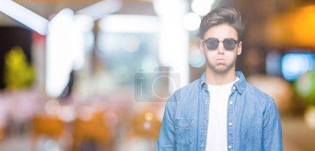 Photo pour Jeune homme beau portant des lunettes de soleil sur fond isolé joues gonflées avec un visage drôle. Bouche gonflée avec de l'air, expression folle . - image libre de droit