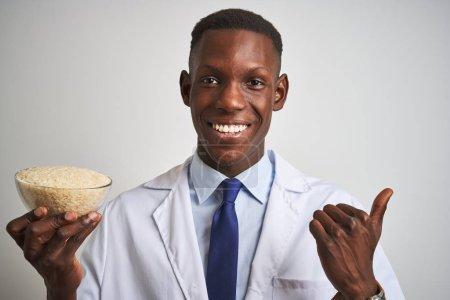 Photo pour L'homme de fixation de docteur américain africain retenant le cuvette avec le riz restant au-dessus du fond blanc d'isolement pointant et affichant avec le pouce vers le haut au côté avec le sourire heureux de visage - image libre de droit