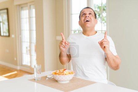 Photo pour Homme d'âge moyen mangeant le riz à la maison étonné et étonné levant et pointant avec des doigts et des bras levés. - image libre de droit