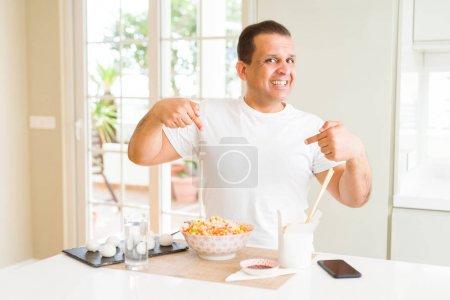 Photo pour Homme d'âge moyen mangeant la nourriture asiatique avec des baguettes à la maison regardant confiant avec le sourire sur le visage, se pointant avec des doigts fiers et heureux. - image libre de droit