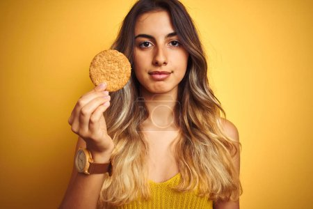 Young beautiful woman eating biscuit over grey iso...