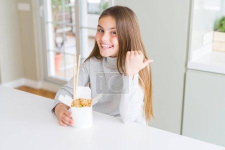 Photo pour Beau jeune gosse de fille mangeant le riz asiatique dans le pointage de boîte de livraison et affichant avec le pouce vers le haut au côté avec le sourire heureux de visage - image libre de droit