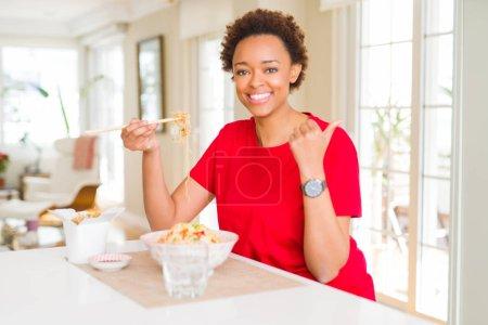 Photo pour Jeune femme américaine africaine avec le cheveu afro mangeant la nourriture asiatique à la maison pointant et affichant avec le pouce vers le haut au côté avec le sourire heureux de visage - image libre de droit
