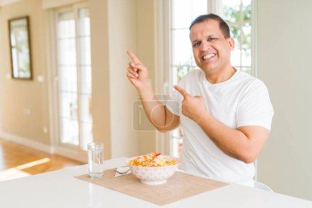 Photo pour Homme d'âge moyen mangeant le riz à la maison souriant et regardant l'appareil-photo pointant avec deux mains et doigts au côté. - image libre de droit