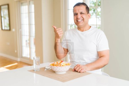 Photo pour Homme d'âge moyen mangeant le riz à la maison souriant avec le visage heureux regardant et pointant vers le côté avec le pouce vers le haut. - image libre de droit