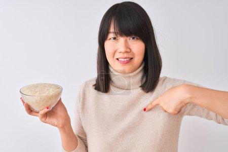 Photo pour Jeune belle femme chinoise retenant le cuvette avec le riz au-dessus du fond blanc d'isolement avec le visage de surprise pointant le doigt à lui-même - image libre de droit