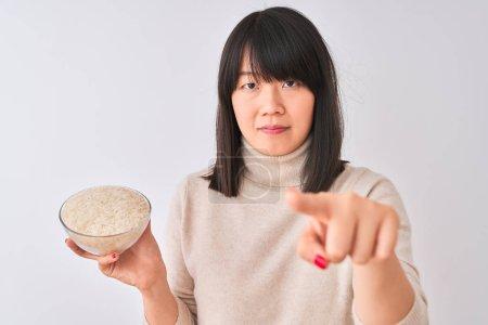 Photo pour Jeune Chinoise tenant un bol avec du riz sur un fond blanc isolé pointant du doigt vers la caméra et vers vous, signe de la main, geste positif et confiant de devant - image libre de droit