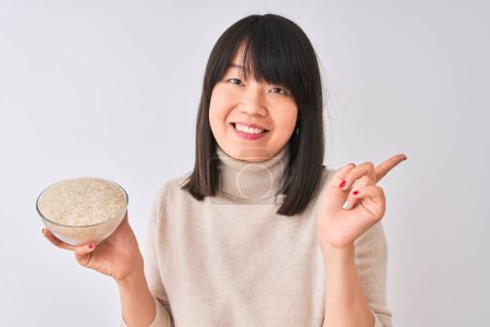 Photo pour Young beautiful Chinese woman holding bowl with rice over isolated white background very happy pointing with hand and finger to the side - image libre de droit