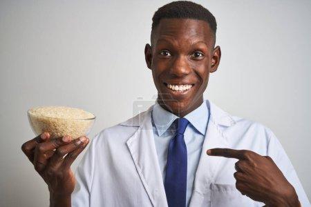 Photo pour Un médecin africain américain tenant un bol de riz debout sur un fond blanc isolé avec un visage de surprise pointant du doigt vers lui-même - image libre de droit