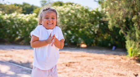 Photo for Adorable blonde child smiling happy. Standing with smile on face walking around the park - Royalty Free Image